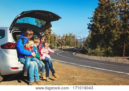 happy family with tree kids travel by car on road, family travel