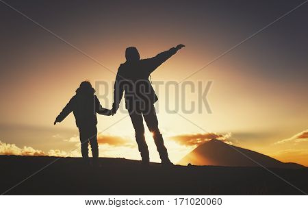 lhouettes of father and son hiking in sunset mountains