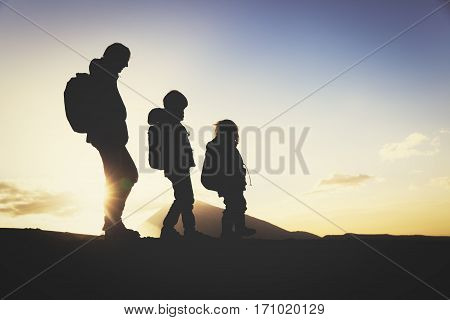 Silhouettes of father and two little kids hiking in sunset mountains