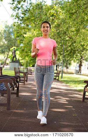 young woman speed walking in the park
