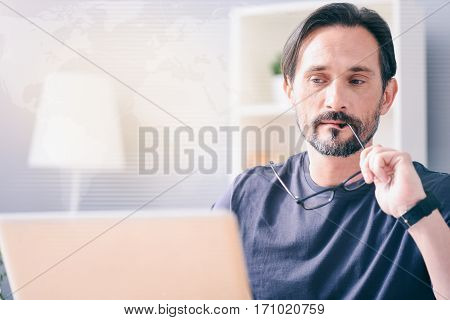 In search of ideas. Pleasant thoughtful man sitting at the table and using laptop while being involved in thoughts
