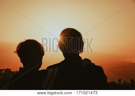 father and little son looking at beautiful sunset