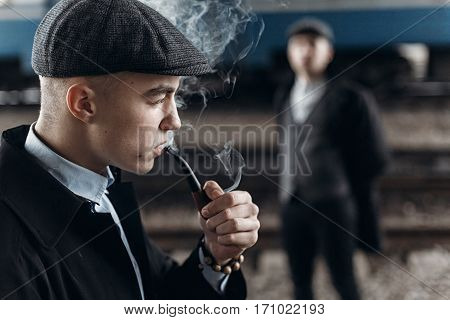 Brutal Gangsters Smoking And Posing On Background Of Railway. England In 1920S Theme. Fashionable Co
