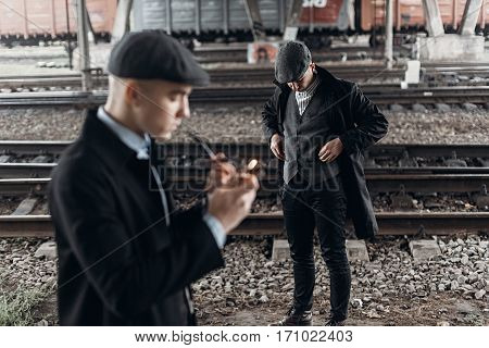 Stylish Gangsters Men, Smoking Pipe On Background Of Railway. England In 1920S Theme. Fashionable Br