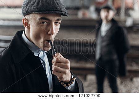 Stylish Man In Retro Outfit, Smoking Wooden Pipe. Sherlock Holmes Look.  England In 1920S Theme. Fas