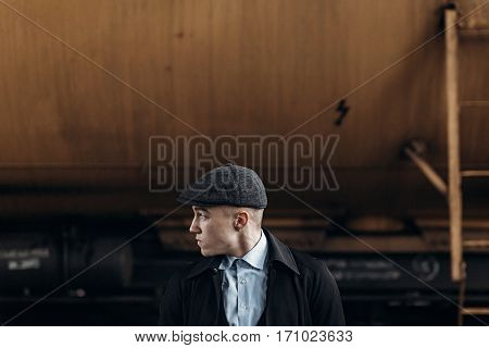 Stylish Man In Retro Look Posing On Background Of Railway. England In 1920S Theme. Fashionable Bruta