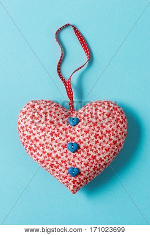 Buttoned Heart-shaped Stuffed Ornament Over Green Background