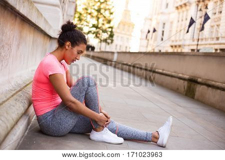young woman feeling her painful ankle after exercise