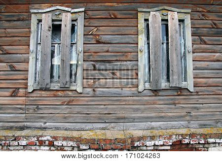 Broken And Boarded Windows Of An Old Abandoned Farmhouse