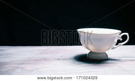 Empty white porcelian teacup. Close-up. Black background