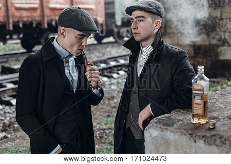 Stylish Gangsters Men, Smoking. Posing On Background Of Railway With Bottle Of Alcohol. England In 1