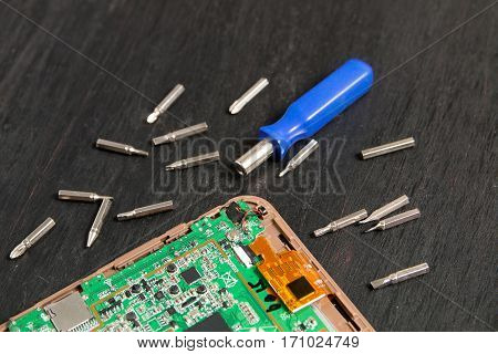 Process of PC Tablet device repair near screwdriver and bit on black wooden background.  Disassembled. Close up.
