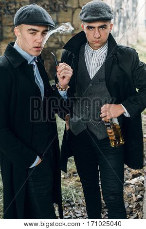 Stylish Gangsters Smoking In Tweed Outfit Posing On Background Of Railway Carriage. England In 1920S