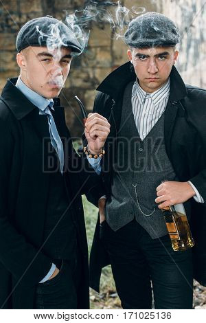 Stylish Gangsters Smooking And Holding Whiskey In Retro Look Posing On Background Of Railway. Englan