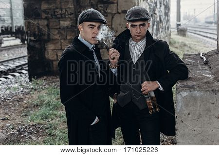 Stylish Gangsters Men, Smoking. Posing On Background Of Railway With Bottle Of Alcohol.sherlock Holm