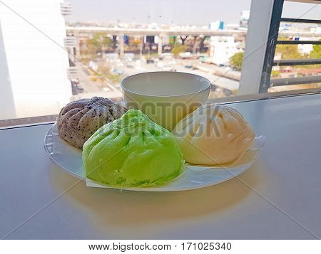 steamed dumpling on white background,Health Benefits of Matcha Tea steamed dumpling,?Black sesame steamed dumpling.The three steamed dumpling on city landscape background.