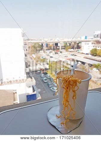 Concept of instant food, Cup noodles instant vegetarian noodles in plastic cup spilled over rustic wood table with plastic fork,Instant noodles spicy Tom Yum Goong on city landscape,economize food.