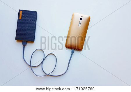 Smart phone is charging with power bank,The wires are arranged into a heart shape for Valentine,Power bank with cable for charging smart phone and digital camera.