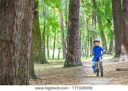 Happy Kid Boy Of 4 Years Having Fun In Autumn Or Summer Forest With A Bicycle On Beautiful Fall Spri