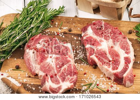 Porky steak with salt pepper and rosemary on wood background. Top view.