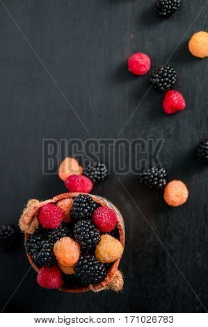 Mixed of red, black, yellow raspberries in a basket on black wooden background. Close up. Top view. Copy spase.