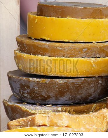 Large round pieces of yellow and brown beeswax