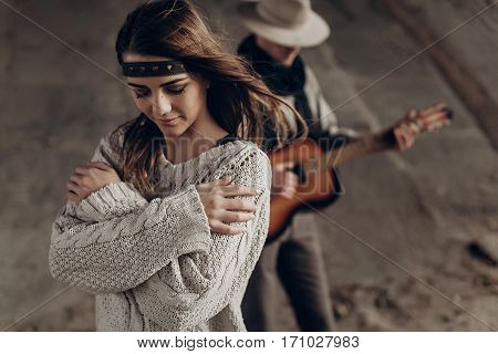 Stylish Hipster Couple Posing. Man In Hat Playing Guitar For His Boho Woman In Knitted Sweater. Atmo