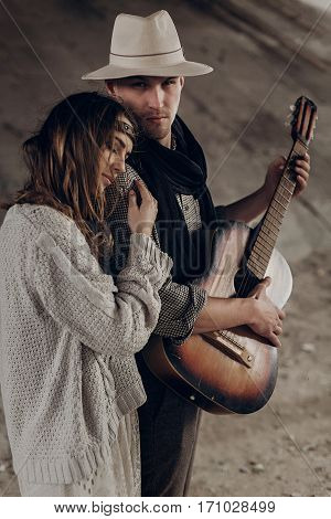 Handsome Musician Man With Guitar And Cowboy Hat Hug With Sensual Brunette Hipster Woman