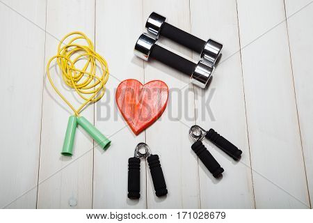 Heart dumbbells skipping rope and the expander on a white wooden background