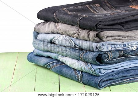 a stack of jeans on a green blue wooden background.