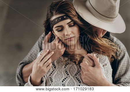 Stylish Hipster Couple Gently Hugging. Man In Hat Sensual Touching Boho Woman In Knitted Sweater. At