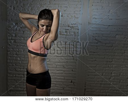 young beautiful and sexy woman in fitness top and shorts with perfect abdomen posing isolated on dim light interior background in healthy lifestyle sport and diet concept