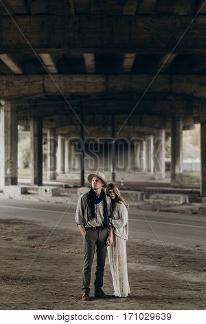 Stylish Hipster Couple Gently Hugging. Man In Hat And Boho Woman In Knitted Sweater Under Abandoned
