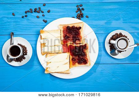 Breakfast toast jam with berries and two cups of coffee on a wooden blue background