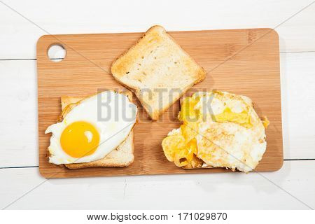 Toasts and egg on a white wooden table