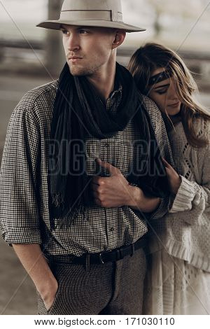 Romantic Gypsy Woman In Stylish Boho Clothes And White Dress Hugging Handsome Cowboy Man In White Ha