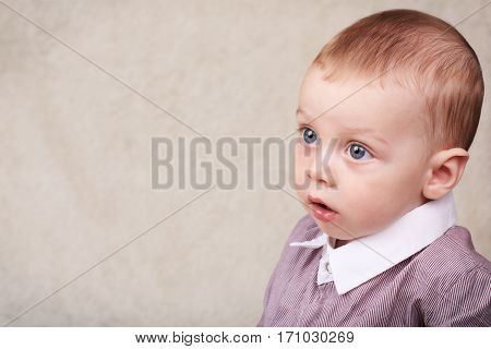 Beautiful baby boy wearing collared shirt looking into copy space with his large blue eyes and short brown hair.