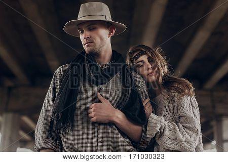 Stylish Hipster Couple Dreaming Under Abandoned Bridge. Boho Gypsy Woman Gently Hugging Arm Of Confi