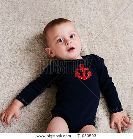 Cute caucasian baby boy wearing a navy sailor outfit with large blue eyes and a beautiful smile with a red anchor embossed onto the chest of the outfit.