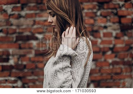 Stylish Hipster Gypsy Woman Posing In Knitted Sweater On Background Of Brick Wall. Atmospheric Windy