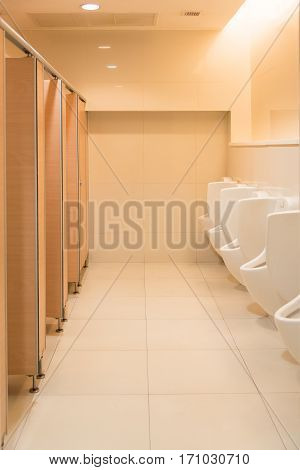 Public clean modern white male toilet restroom with urinals interior idea concept background