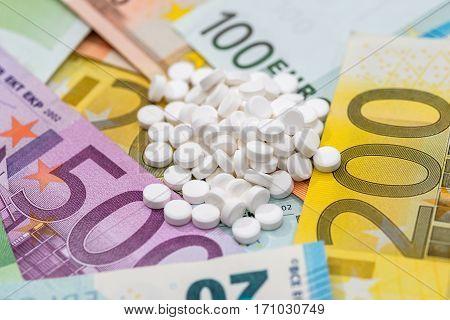 different pills above euros bills. close up.