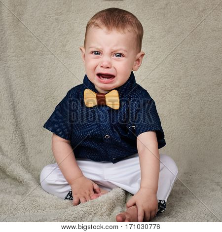 Cute baby boy wearing a navy shirt, white pants, and a wooden bowtie sitting on a beige blanket while crying and looking into camera.