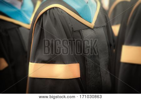 Selective focus on gowns of bachelor degree graduates in commencement graduation ceremony row metaphor education success concept background