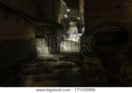 on the evening rushing water fall down from a factory
