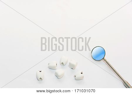 Dental care concept top view or flat lay of helathy teeth and bad teeth or caries with dentist mirror with copy space background on white