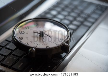 Black clock lay on keyboard time metaphor concept in dark low key tone selective focus.