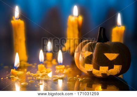 Halloween spooky Jack-O-Lantern pumpkin head with candles decoration at night background selective focus