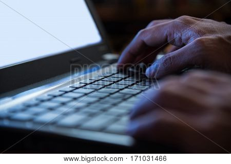 Selective focus on man two hand typing laptop/PC/computer keyboard in night dark tone low key