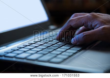 Selective focus on man hand typing laptop/PC/computer keyboard in night dark tone low key